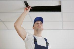 man checking ceiling tiles